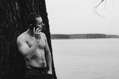 Young Naked Man. Young man with phone near the tree on lake. Black and white photo Royalty Free Stock Photo
