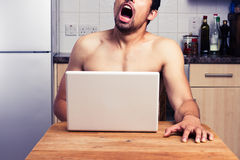 Young naked man watching porn in his kitchen Royalty Free Stock Photo