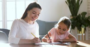 Young nanny drawing pictures in paper album with daughter.