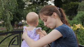 A young nanny looking at the smartphone screen, tucking her hair, putting the smartphone aside and moving a baby girl stock video footage