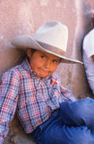 Young Native American boy sitting. Young Native American cowboy lying on ground, Gallup, New Mexico stock photography