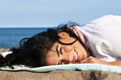 Young native american woman at beach. Portrait of beautiful smiling native american girl laying at beach Stock Photos
