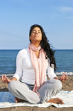Young native american woman meditating. Portrait of beautiful native american girl doing yoga at beach Royalty Free Stock Image