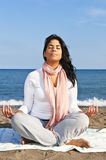 Young native american woman meditating. Portrait of beautiful native american girl doing yoga at beach Stock Photo