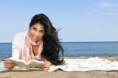 Young native american woman reading. Portrait of beautiful smiling native american girl reading book at beach Stock Photo