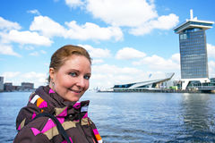 Young native dutch woman on a ferry in the harbor from Amsterdam. Young native dutch woman in the harbor from Amsterdam in the Netherlands Royalty Free Stock Photo