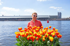 Young native dutch woman smelling blossoming tulips in the harbo. R from Amsterdam Stock Photo