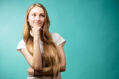 Young natural lookingcaucasian girl, different poses, emotions on blue backgrounds. Young natural looking girl in different poses shows different emotions on royalty free stock photography