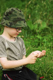 Young natural scientist. Little boy with bug in graas Stock Photos