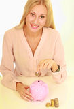 Young natural woman holding piggy box ,standing in office Royalty Free Stock Images