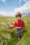 The young naturalist. With magnifier glass on alpine meadow Royalty Free Stock Image