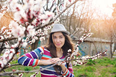 Young naturally beautiful woman near the blooming tree in spring time. Stock Image