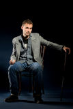 Young negligent man with cane sitting on chair Royalty Free Stock Photo