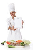 Young nepalese man chef, menu, fresh vegetables. Young attractive nepalese man chef showing the menu list, blank page. Variety of fresh vegetables on table stock photography