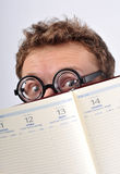Young nerd hiding behind agenda Royalty Free Stock Photo