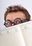 Young nerd hiding behind agenda. Caucasian young nerd hiding behind open agenda Royalty Free Stock Photo