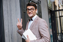 Young nerd man in eyeglasses showing v sign Royalty Free Stock Photography