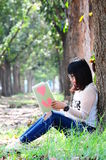 Young Nerd Woman Reading Book of Love in Park.  royalty free stock image
