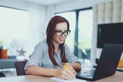 Young nerd woman writing notes indoors stock photo