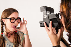 Young nerdy girls using instant camera. Stock Images