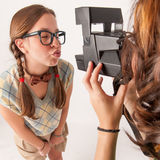 Young nerdy girls using instant camera. Royalty Free Stock Image