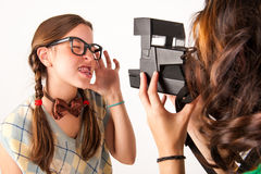 Young nerdy girls using instant camera. Royalty Free Stock Photos