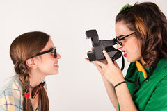 Young nerdy girls using instant camera. Stock Photography