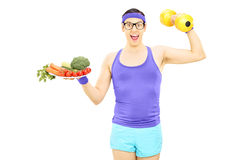 Young nerdy guy holding plate with vegetables and a dumbbell Stock Photo