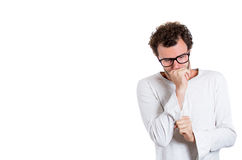 A young nerdy looking guy lost in thoughts Stock Image