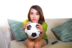 Young nervous and beautiful football fan woman watching television game sitting on sofa couch holding soccer ball excited highly c royalty free stock photos