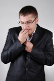 Young nervous businessman biting his fingers Royalty Free Stock Image