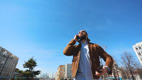 A young nervous man emotionally talks on several telephones. A guy with a beard and glasses nervously talking on the stock footage