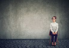 Young nervous woman sitting on chair stock photography
