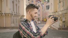 Young newbie bearded photographer taking a photo in the street of an old city with beautiful architecture. Tourist takes. Young newbie bearded photographer stock video