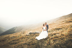 Young newly wed couple, bride and groom kissing, hugging on perfect view of mountains, blue sky Royalty Free Stock Image