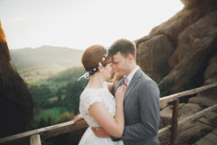 Young newly wed couple, bride and groom kissing, hugging on perfect view of mountains, blue sky Royalty Free Stock Photo