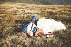 Young newly wed couple, bride and groom kissing, hugging on perfect view of mountains, blue sky Royalty Free Stock Photos