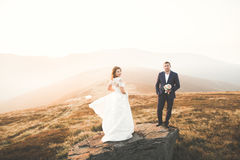 Young newly wed couple, bride and groom kissing, hugging on perfect view of mountains, blue sky Stock Image