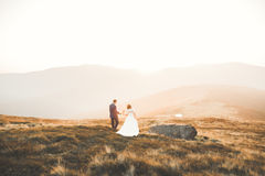Young newly wed couple, bride and groom kissing, hugging on perfect view of mountains, blue sky Stock Photography