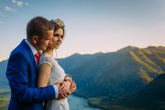 Young newly wed couple, bride and groom kissing, hugging on perfect view of mountains, river and blue sky royalty free stock images