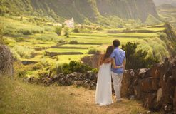 Young newly wedded hugging couple in honneymoon on Flores island, Azores. Young newly wedded couple in honneymoon on background of beautiful view of Flores royalty free stock photo