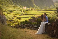 Young newly wedded kissing couple in honneymoon on Flores island, Azores. Young newly wedded couple kissing in honneymoon on background of beautiful view of royalty free stock photography