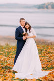 Young newlywed bridal couple holding each other on autumn lakeshore full of orange leaves.  Stock Photography