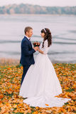 Young newlywed bridal couple holding their hands on autumn lakeshore full of orange leaves Stock Photos