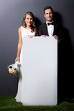 Young newlywed couple holding white board Stock Photography
