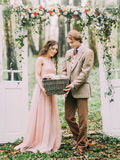The young newlywed couple is holding the woven box under the white arch in the form of two doors decorated with red and. White flowers. The wood location Royalty Free Stock Photo
