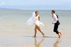 Young newlywed couple playfully at the beach Royalty Free Stock Photos