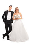 Young newlywed couple posing together. Full length portrait of a young newlywed couple posing together isolated on white background Royalty Free Stock Images