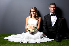 Young newlywed couple sitting on the  grass Royalty Free Stock Photos