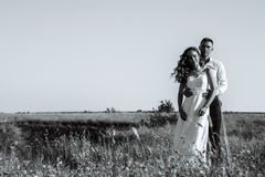 Young newlywed couple walking in field in sunlight outdoor. Young newlywed couple of women in wedding dress and men walking in field in sunlight outdoor, black Royalty Free Stock Photography
